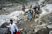 Hindu pilgrims assist each other while walking along the glaciers enroute to the revered Hindu pilgrimage, the Amarnath yatra in Kashmir, India. Hindu pilgrims brave sub zero temperature and high latitude passes and make their pilgrimage to reach the sacred Amarnath cave, which houses a lingam - a stylized phallus, worshiped by Hindus as a symbol of God Shiva. Photo: Sanjit Das/Panos