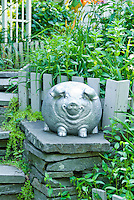 Ornamental pig statue in garden next to steps, atop stone wall column, potbellied pig