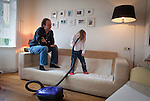 Nederland, Amsterdam , 29-01-2009 - Vader en dochter van vier jaar dollen met de stofzuiger. (model released) . Foto: Gerard Til