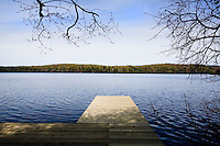 A jetty leading from the house projects out over the tranquil waters of Bark Lake in the Laurentian Mountains north of Montreal