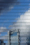 Abstract skyscraper facade with reflection of skyline and clouds.