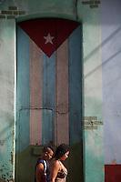 Cuba , l'Avana Vecchia, un ragazzo e una signora passano davanti a una porta con bandiera cubana d