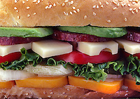 SUBMARINE SANDWICH with swiss cheese, tomatoes, cheader cheese, lettuce, avacado, salami, onions and pickle