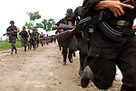 FARC rebels run in formation down a road just outside of San Vicente del Caguan in the former FARC controlled zone of Colombia. The FARC are Colombia's oldest and largest rebel group numbering over 18,000 rebels. (Photo/Scott Dalton)