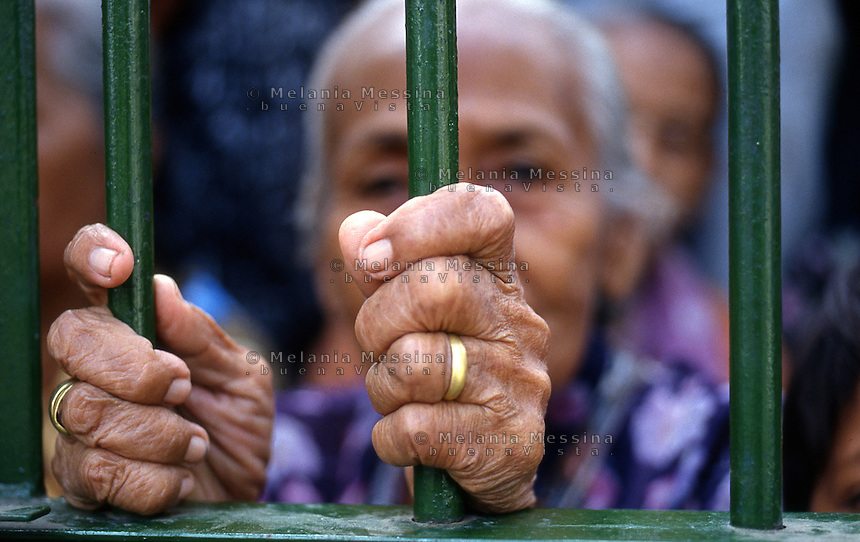 Yogyakarta,Indonesia, a woman  behind the gates of the palace of the Sultan to attend the celebration of the birth of Muhammad.<br /> Yogyakarta, Indonesia, un'anziana donna dietro ai cancelli del palazzo del sultano per assistere alle celebrazioni della nascita di Maometto.