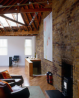 One wall painted white creates a contrasting note highlighting the exposed beams and brick walls in this open plan living room