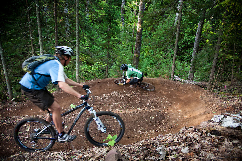 Mountain bikers on the signature bermed and banked turns of The Flow trail of Copper Harbor Michigan.
