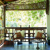 A wooden bench has been placed at the end of a cool and shady porch