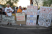 Phoenix, Arizona. June 23, 2012 - Members of the Unitarian Universalist church and community advocates gathered outside the Tent City Jail in Arizona to demand  Sheriff Joe Arpaio to shut down what they call a &quot;concentration camp&quot; and inhumane outdoor jail facility. Tent City houses inmates in canvas tents and during the summer the temperature raises significantly under the tents. In this image, activists Rob McElwain (left) and Jorge Mendez (orange shirt),  long-time opponents of Sheriff Joe Arpaio, hold sign across the street where Arpaio was talking to reporters. Photo by Eduardo Barraza &copy; 2012