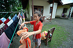 Tri Sabarian Hia, 11, hangs laundry to dry in front of her home in Tugala, a village on the Indonesian island of Nias. <br /> <br /> The village was struck by both a 2004 tsunami and a 2005 earthquake, leaving houses destroyed and lives disrupted. The ACT Alliance helped villagers here to construct new homes and latrines, build a potable water system, open a clinic and schools and get their lives going once again. For the residents of Tugala, the post-disaster mantra of &quot;build back better&quot; became a reality with help from the ACT Alliance.