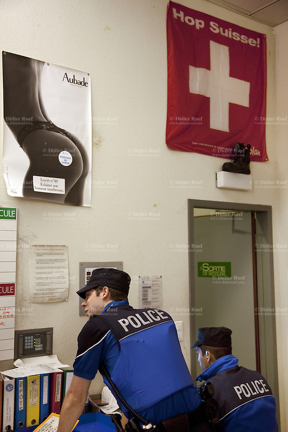 Switzerland. Geneva. Paquis police station. Two police officers check on a computer the identities of men who haver been earlier arrested. A swiss flag and a poster for Aubade lingerie ( a beautiful naked woman with a sexy underwear ) are on the wall. A policeman's shoe is placed on a lamp above the door. A police station or station house is a building which serves police officers and contains offices, locker rooms, temporary holding cells and interview/interrogation rooms. Both policemen are wearing a ballistic vest, bulletproof vest or bullet-resistant vest which is an item of personal armor that helps absorb the impact from knives, firearm-fired projectiles and shrapnel from explosions, and is worn on the torso. Soft vests are made from many layers of woven or laminated fibers and can be capable of protecting the wearer from small-caliber handgun and shotgun projectiles, and small fragments from explosives such as hand grenades. The flag of Switzerland consists of a red flag with a white cross (a bold, equilateral cross) in the centre. It is a sovereign-state flag. 4.05.12 © 2012 Didier Ruef