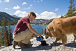 A woman gives water to her golden retriever at Lower Echo Lake, El Dorado National Forest, California