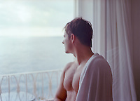 man with a towel drapped over shoulder looking out of a balcony window