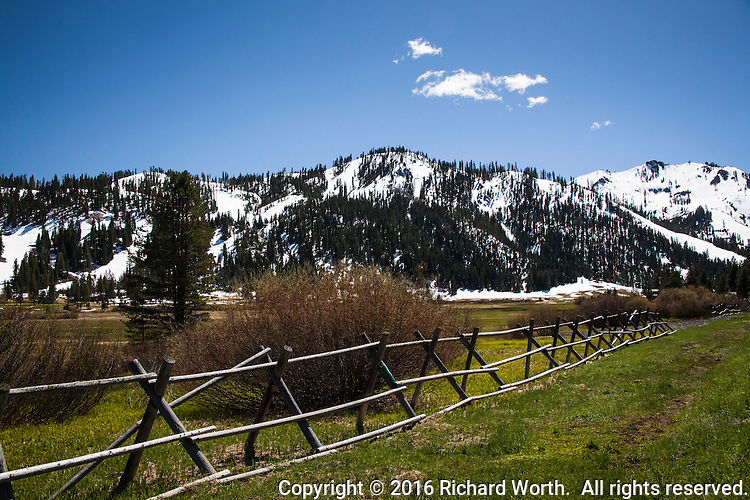 Snow covered mountains and a rustic wooden fence are highlights of a spring meadow scene in California's Sierra Nevada Mountains.