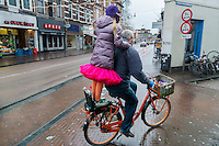 Fietser met meisje staand achterop de fiets door de regen van de Nobelstraat naar de Nobeldwarsstraat Utrecht.