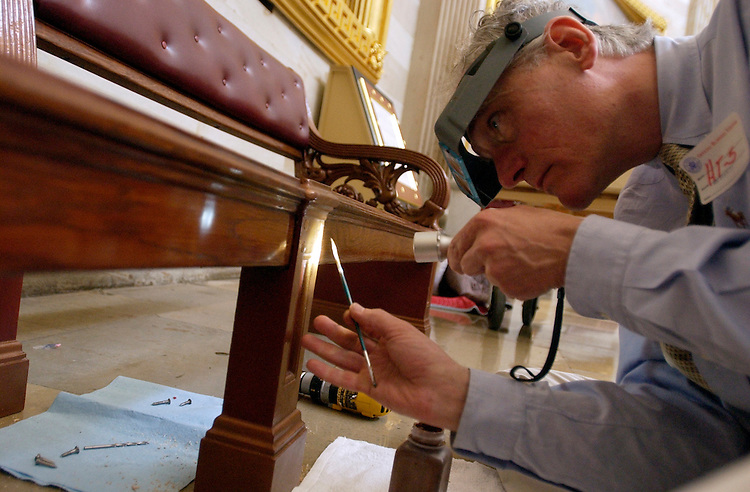 Bruce Schuettinger, a furniture conservator working under contract with the Architect of the Capitol, installs a historic bench in the Capitol Rotunda.  The bench, and others like it, were designed in 1859 and used in the House Chamber for one year.