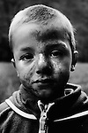 Young boy with face covered in mud.
