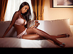 Beautiful sexy young black woman in pink lingerie sitting on a sofa in a dimly lit room