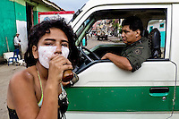 A young Colombian girl gets high by sniffing the shoe glue in front of the Police patrol in the slum of Calvario, Cali, Colombia, 23 April 2004. Calvario, a slum right in the centre of the city, is considered the social bottom of Cali society. Poor dwellers recollect the garbage in the near city centre to sell it for recycling, while their children get high by sniffing the shoe glue on the dirty streets of ghetto. The order in Calvario is maintained by the illegal authorities, usually former policemen or army members, who set their own rules. Criminality, drug abuse, unemployment never allow the slum people jump off the misery and stop being the second category citizen within the rigid society of Colombia. Although Christian missionary organizations attempt to provide help, the overall situation does not improve.