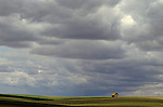Old weathered barn in rolling fields with storm clouds Eastern Washington State USA