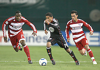 Andy Najar #14 of D.C. United races away from Edson Edwards #27 and Bruno Guarda #8 of F.C. Dallas during a US Open Cup match on April 28 2010, at RFK Stadium in Washington D.C. United won 4-2.