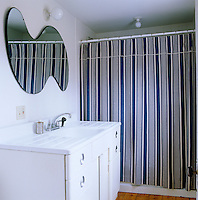 A bold blue and taupe striped shower curtain makes a statement in this small bathroom