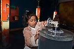 Oakland CA 2nd grade girl on school field trip to Chabot Space and Science Center manipulating a crank to create a vortex