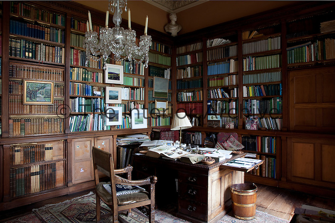 The antique desk in the book-lined study overflows with books and papers