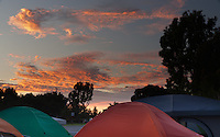 The sunset illuminates clouds in a brilliant orange over the tops of tents at Occupy Orange County in Irvine, CA.