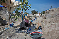 Indonesia - Bangka Island - A woman washing tin out of sand and water. The mine where she works  hosts hundreds of workers, from suckers to washers to tin scrappers. The previous night, a miner who had worked all night was carrying two sacks of tin. Police took it when he was coming out of the mine. Sometimes, all the workers are arrested and jailed, and only the owner of the pontoon can redeem them, if he has enough money.