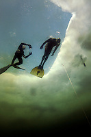 Steinar Schjager descends as Terje Brandshaug lloks on.Freediving under the ice at Lutvann lake,outside Oslo, Norway. Photo: Fredrik Naumann/Felix Features