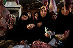 Women bargain for meat at Al Rasaffa market in Sadr City, Baghdad, Iraq, May 27, 2010. Appeals of some of Iraq's winning candidates in the parliamentary election nearly three months ago continued to stall the process of forming a new government.