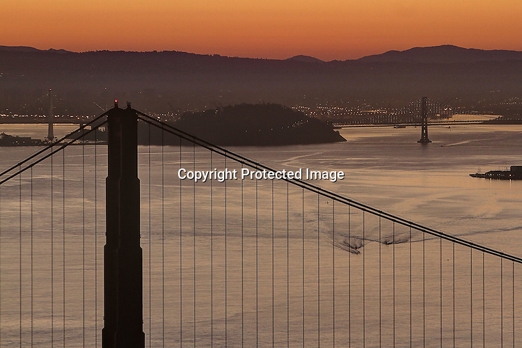 The sunrises over the northern tower of the Golden Gate Bridge as seen from the Marin Headlands, Sausalito, CA.