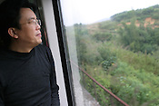 Chinese writer Zhang Zhe, as he travels on the 30 hour train trip between Kunming and Guangzhou as part of the Think UK Writers Train project. The Think UK China Writers Train is a project, in collaboration with the British Council, to take 4 UK writers/poets and 4 Chinese writers/poets around China by train visiting 6 major cities, in 17 days, to hold talks, seminars and readings of their work.