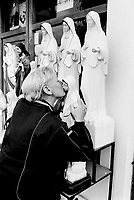 Bosnia. Medjugorje. A pilgrim woman kisses the Virgin Mary' statue , among other statues like the one of Jesus Christ which are on sale in a tourist shop. A picture from the italian Padre Pio is on display in the window. © 2002 Didier Ruef