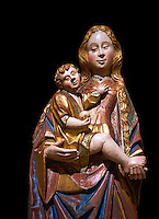 Gothic statue of The Virgin Mary (Madonna) holding the baby Jesus. Polychrome and gold leaf on wood by the Circle of Gil de Siloe around 1500, probably from Castella. Inv MNAC 64028. National Museum of Catalan Art (MNAC), Barcelona, Spain. Against a black background.