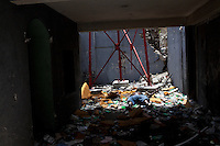 The body of a dead man lies amid earthquake rubble on July 8, 2010 in Port-au-Prince, Haiti. Several bystanders claimed he had been shot three days before by the police, for crimes unknown.