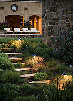 Califronia home with pathway and stone steps with night lighting leading to outdoor living patio with chairs
