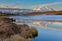 Morning fog over Wonder lake at sunrise, Denali looms in the distance and reflects in the calm waters, Denali National park, Alaska.