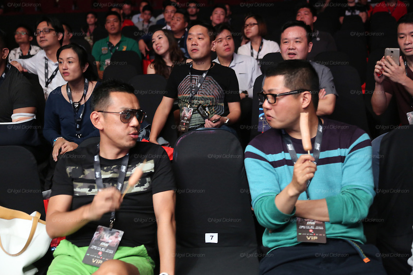 Young men in VIP section eating sausages whilst watching the fight<br />