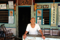 Singapore. Pulau Ubin island. An old chinese man (95 years ) has been living his entire life in the same house. Chinese writings on the wall. © 2001 Didier Ruef