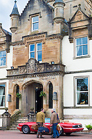 Concierge assists hotel guest on arrival at the highland Cameron House Hotel by Loch Lomond, north of Glasgow in the Highlands of Scotland