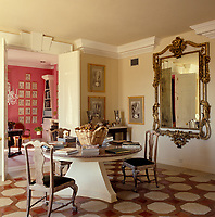 A large antique mirror hangs on the wall of this dining room which features a geometric parquet and tile floor