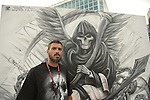 Garden City, New York, USA. September 14, 2014. DAN AZACETA, aka JOUST201, from New Jersey, is a graffiti artist creating a black and white outdoor mural of the Grim Reaper, at the United Ink Flight 914 tattoo convention at the Cradle of Aviation museum of Long Island.