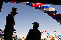 """Tempe, Arizona. October 13, 2012 - The silhouette of a man dressed as """"Uncle Sam"""" who was standing on stilts was one of the attractions of a colorful non-partisan political rally where hundreds of registered voters learned more about local and presidential candidates. Hundreds of Arizona registered voters participated in a political rally where candidates for the US Senate, House of Representatives, state legislature, Maricopa County and other public offices pitched for votes for the upcoming general election. Photo by Eduardo Barraza © 2012"""