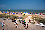 Happy vacationers wander the beach and walk the boardwalk on the first day of summer at Rehoboth Beach, Delaware.
