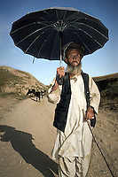 A shepherd uses an umbrella to shield himself from the sun as he leads his sheep.