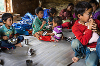 Aakash Tamang (centre), 9, feeds another child after his lunch in the SOS Children's Villages Child Care Space canteen in Rayale, Nepal on 1 July 2015. The Child Care Space was set up by SOS Children's Villages soon after the earthquake so that the children of the village can come together to play, learn, and get over the trauma of the disaster as well as get regular daily meals. This also allows their parents to be free to reconstruct their homes and go off to get rations and relief kits. Photo by Suzanne Lee for SOS Children's Villages