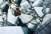 Technician in a crane basket being lowered from an icebreaker research ship to retrieve an unmanned submersible (yellow) trapped beneath pieces of Arctic Ocean sea ice.