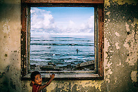 A child stands at the window opening in one of the many derelict houses on the island.
